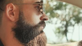 Зверский бородатый человек в солнечных очках управляет автомобилем сток-видео