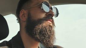 Зверский бородатый человек в солнечных очках управляет автомобилем видеоматериал