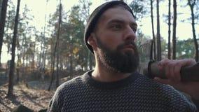 Зверский бородатый человек с осью на его плече смотря далеко вперед Небритый парень с осью в лесе сток-видео