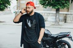 Зверский и мышечный велосипедист бороды на мотоцикле Стоковая Фотография