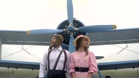 Зверский пилот в шлеме стоит рядом с женщиной в розовом платье стоя около старого самолета с пропеллером сток-видео