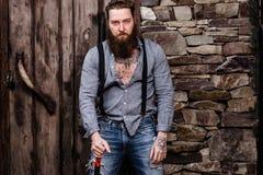 Зверский сильный человек с бородой и татуировки на его руках одетых в стильных стойках случайных одежд на предпосылке  стоковое фото