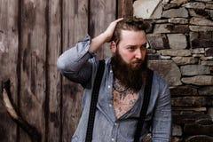Зверский сильный человек с бородой и татуировки на его руках одетых в стильных стойках случайных одежд на предпосылке  стоковые изображения rf