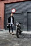 Зверский человек около его мотоцилк таможни гонщика кафа Стоковые Изображения