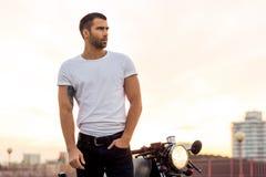 Зверский человек около его мотоцилк таможни гонщика кафа Стоковое Фото