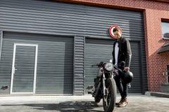 Зверский человек около его мотоцилк таможни гонщика кафа Стоковая Фотография RF