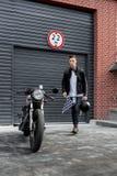 Зверский человек около его мотоцилк таможни гонщика кафа Стоковое Изображение