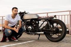 Зверский человек около его мотоцилк таможни гонщика кафа стоковое фото rf