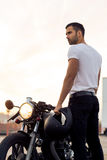Зверский человек около его мотоцилк таможни гонщика кафа Стоковые Фото