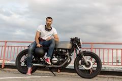 Зверский человек сидит на мотоцилк таможни гонщика кафа Стоковые Изображения