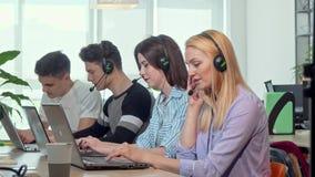 Звонки красивой молодой женщины отвечая, работая в центре телефонного обслуживания работы с клиентом акции видеоматериалы