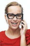 Звонки молодой женщины на сотовом телефоне стоковое фото rf