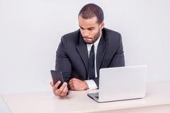 Звонок клиента Усмехаясь африканский бизнесмен сидя на столе и Стоковая Фотография