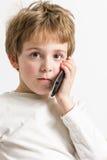 звонок мальчика слушая меньший телефон Стоковые Изображения RF