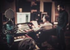 Звукооператор и производитель работая совместно на смешивая панели в студии звукозаписи бутика стоковое фото
