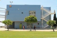 Здание, деревья и студенты в университетском кампусе стоковое изображение rf