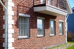 Здание красного кирпича Белый балкон Белизна Windows цветочных горшков стоковые фото