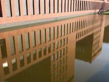 Здание отраженное в воде Стоковые Изображения