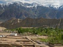 Здания глины в высоком горном селе в Гималаях среди высоких горных цепей под пасмурным небом лета Стоковая Фотография