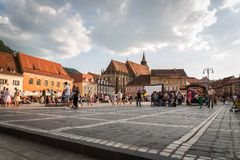 Здания и люди в главной площади, Brasov, Румыния Стоковое Изображение RF
