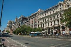 Здания на оживленной улице с людьми и автобусом в Мадриде стоковые фото
