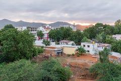 Здания на предпосылке захода солнца, Puttaparthi, Андхра-Прадеш, Индии Скопируйте космос для текста Стоковые Фотографии RF