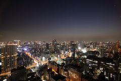 здания осветили токио захода солнца дорог Стоковая Фотография