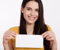 здесь текст ваш Милая молодая женщина держа пустую пустую доску Портрет студии на белой предпосылке Модель-макет для дизайна Стоковая Фотография RF