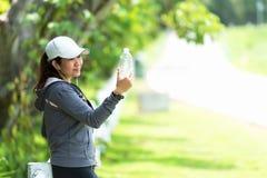 Здоровая атлетическая азиатская женщина выпивает чистую воду от бутылки освежая после тренировки в природном парке стоковая фотография rf