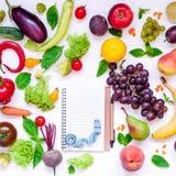 Здоровая еда, диета есть, предпосылка вытрезвителя - различные фрукты и овощи, опорожняет открытую тетрадь, и измеряя лента на бе стоковая фотография rf