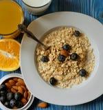 Здоровая еда, еда и концепция диеты - вкусная овсяная каша с ягодами и стеклом апельсинового сока стоковые изображения