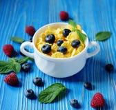 Здоровая еда, еда и концепция диеты - корнфлексы с полениками и голубиками ягод на голубой деревянной предпосылке стоковые изображения