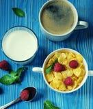 Здоровая еда, еда и концепция диеты - корнфлексы с полениками и голубиками ягод на голубой деревянной предпосылке стоковое изображение