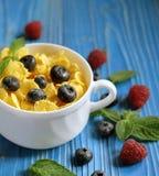 Здоровая еда, еда и концепция диеты - корнфлексы с полениками и голубиками ягод на голубой деревянной предпосылке стоковые фото