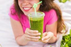 Здоровая еда, лето и концепция людей - молодая женщина имеет потеху в smoothies парка и питья зеленых на конце пикника Стоковое фото RF