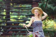 Здоровая женщина Девушка модели лета красоты с яркими цветами bicycle лес и корзина отдых стиля Красивая дама подняла ее Стоковое Изображение RF