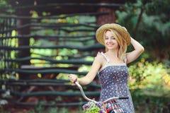 Здоровая женщина Девушка модели лета красоты с яркими цветами bicycle лес и корзина отдых стиля Стоковое Изображение RF