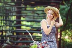 Здоровая женщина Девушка модели лета красоты с яркими цветами bicycle лес и корзина отдых стиля Стоковые Изображения RF