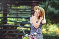 Здоровая женщина Девушка модели лета красоты с яркими цветами bicycle лес и корзина отдых стиля Красивая дама подняла ее Стоковая Фотография