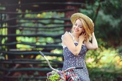 Здоровая женщина Девушка модели лета красоты с яркими цветами bicycle лес и корзина отдых стиля Красивая дама подняла ее Стоковые Фотографии RF