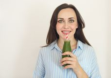 Здоровая женщина представляя с свежей бутылкой сока зеленого smo вытрезвителя стоковые изображения