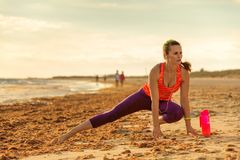 Здоровая женщина пригонки в спорт зацепляет на протягивать берега моря Стоковое Изображение