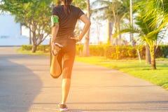 здоровая жизнь Азиатский бегун женщины фитнеса протягивая ноги перед разминкой бега внешней в парке стоковое изображение