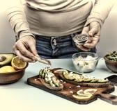 здоровая заедк Женщина подготавливает сандвичи с авокадоом и arugula дома Стоковое Фото