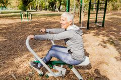 Здоровая зрелая женщина практикуя на на открытом воздухе спортзале стоковое фото rf