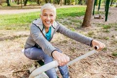 Здоровая зрелая женщина практикуя на на открытом воздухе спортзале стоковое изображение rf