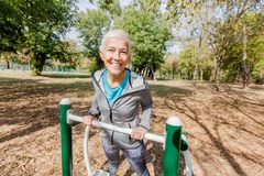 Здоровая зрелая разминка женщины на на открытом воздухе спортзале в лесе стоковые изображения