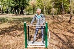 Здоровая зрелая разминка женщины на на открытом воздухе спортзале в лесе стоковое фото rf