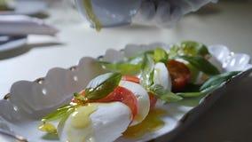 Здоровая концепция еды и вегетарианца Закройте вверх лить оливкового масла над caprese салатом Итальянский caprese салат с сток-видео