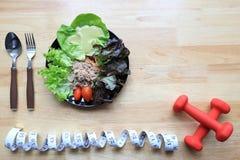 Здоровая концепция еды и фитнеса, взгляд сверху салата овоща с dumbells и измеряя лента на деревянной темной предпосылке стоковые изображения